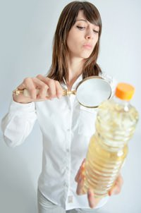 woman-inspecting-oil-bottle-with-magnifying-glass