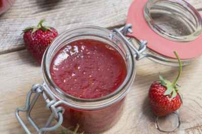 Strawberry jam in a jar on wood