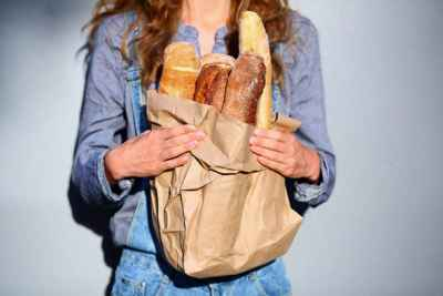 brunette-holding-bag-of-baguettes
