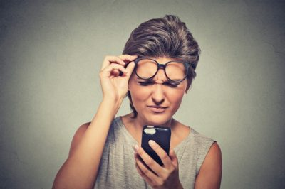 brunette-with-glasses-having-difficulty-reading-cell-phone