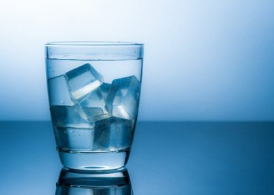 glass-of-water-with-ice-cubes-and-blue-background