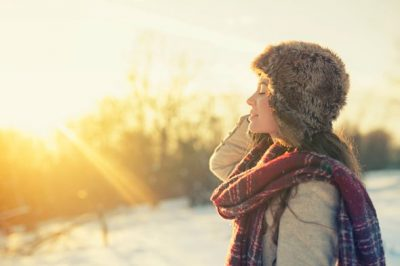 young-woman-outside-on-cold-day-turning-face-towards-sun