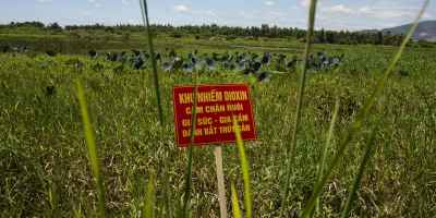 """A warning sign stands in a field contaminated with dioxin near Danang airport, during a ceremony marking the start of a project to clean up dioxin left over from the Vietnam War, at a former U.S. military base in Danang, Vietnam Thursday Aug. 9, 2012. The sign reads; """"Dioxin contamination zone - livestock, poultry and fishery operations not permitted"""". The U.S. and Vietnam on Thursday launched a four-year joint effort to clean up dioxin leftover from Agent Orange that was mixed, stored and loaded onto planes at the former U.S. military base, which is now part of Danang's airport. Dioxin can linger in soils and at the bottom of lakes and rivers for generations, entering the food supply through the fat of fish and other animals. (AP Photo/Maika Elan)"""