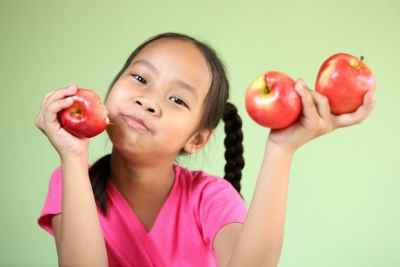 young-girl-holding-three-apples
