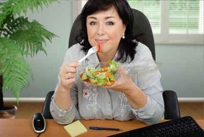 middle-aged-woman-eating-salad-in-office