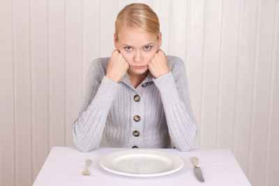 frustrated-blonde-sitting-at-table-with-empty-plate