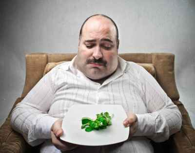overweight-man-looking-down-at-small-meal-of-lettuce-leaves
