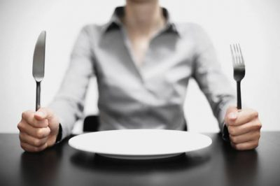 woman-with-an-empty-plate-in-front-of-her-holding-fork-and-knife
