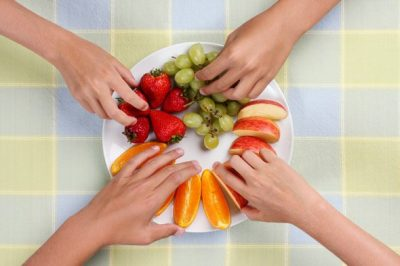 hands-taking-pieces-of-fruit-off-plate