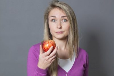 young-blonde-with-questioning-expression-holding-apple