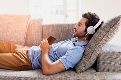 young-man-lying-on-couch-listening-to-music