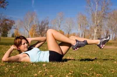 Young woman doing a bicycle ab exercise.